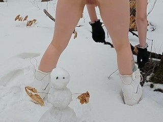 naked girl making snowman in the woods